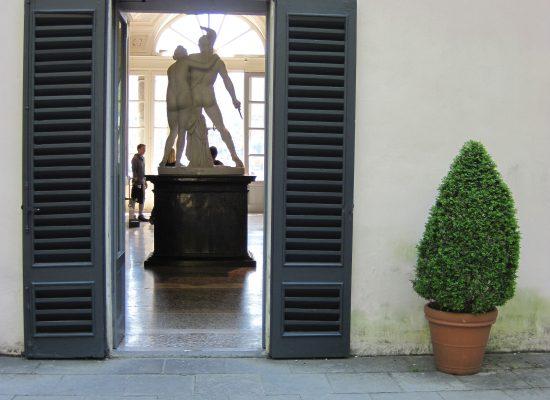 Statue hinter halb geöffneter Flügeltür der Villa Charlotta